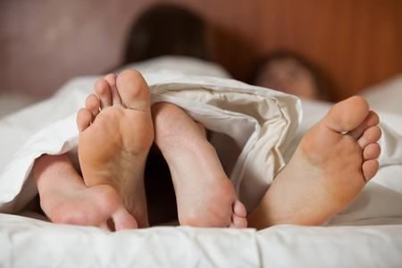 pareja en la cama: Feliz pareja joven duerme en la cama en su casa.