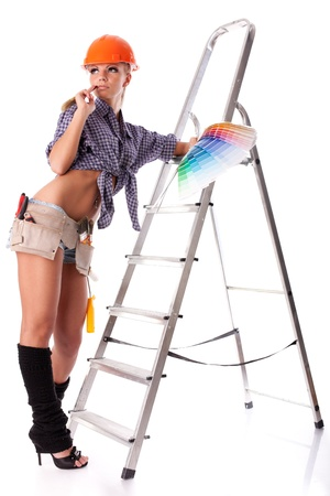 Young woman in hardhat with a color guide and paintbrush on a white background. photo