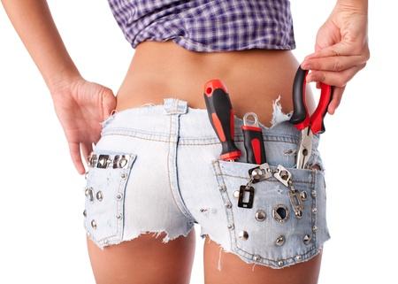 Vrouwelijke werknemer met hulpmiddelen in de rug zak op korte broek op een witte achtergrond.