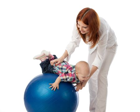 Mother and sweet small baby with fitness ball on a white background. Stock Photo - 9490549