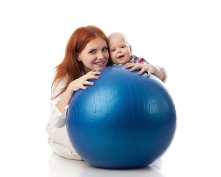 Mother and sweet small baby with fitness ball on a white background.
