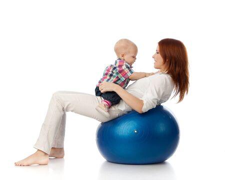 Moeder en lieve kleine baby met fitness bal op een witte achtergrond.