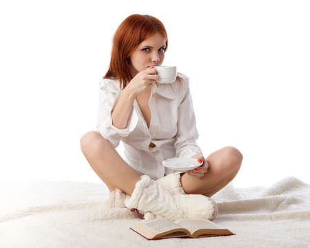 Young woman with  book and cup of coffee sits on warm plaid on a white background. photo