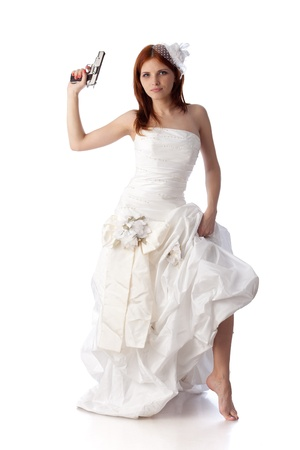 Young woman in a wedding dress with gun on a white background. photo