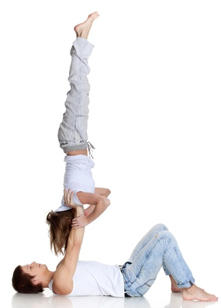 acrobatics: Young sports people carry out acrobatic tricks on a white background. Concept of teamwork. Stock Photo