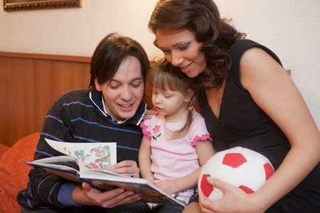 Young parents with their  daughter at home. Happy family. photo