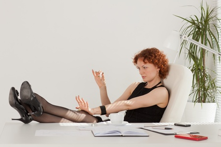 Young businesswoman rests at the table in the office. photo