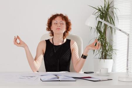 Jonge zakenvrouw mediteren op de werkplek op kantoor.