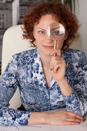 woman handle success: The smiling young businesswoman with a magnifying glass.
