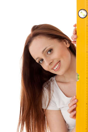 Young female construction worker with yellow level on a white background. photo
