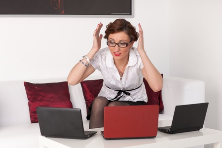 Stressed  young businesswoman with three laptops. photo