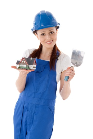 Young woman in  coverall with trowel and model of house on a white background. Female construction worker. Stock Photo - 9676053