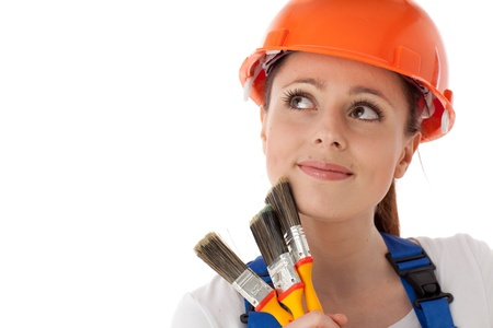 Portrait of young woman in  helmet with paintbrushes on a white background. Female construction worker. Stock Photo - 9675995