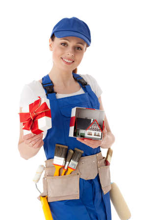 Young woman in  coverall holds gift box with model of house on a white background. Female construction worker. photo