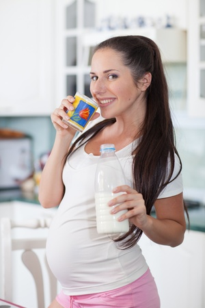 Zwangere vrouw drinkt de melk op de huis-keuken. Stockfoto