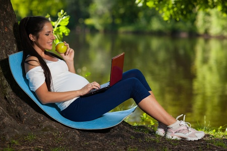 Young beautiful  pregnant  woman with laptop  and an apple  sits in the park. Stock Photo