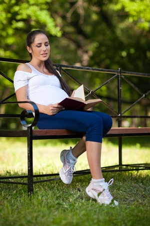 Young beautiful  pregnant  woman with book  sits on the bench in the park. photo