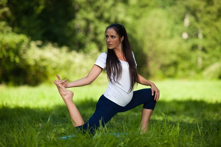 The active pregnant woman does sports exercises in a summer park. Care of health and pregnancy. photo