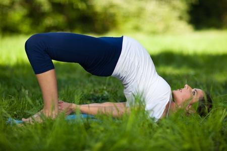 De actieve zwangere vrouw doet sport oefeningen in een zomer park. Zorg voor gezondheid en zwangerschap. Stockfoto