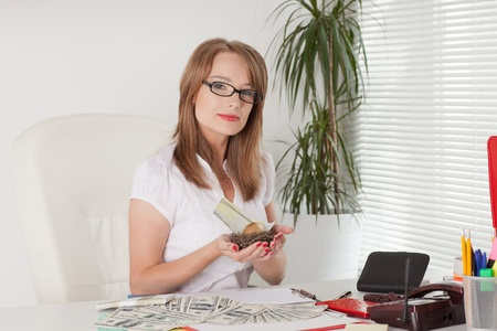 Young businesswoman holds nest with a golden egg and money at the office. Financial concept. photo