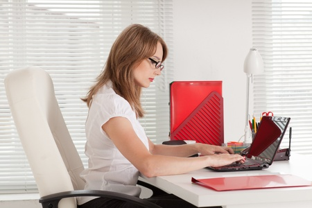 studing: Young businesswoman with laptop sits at the table at the office.