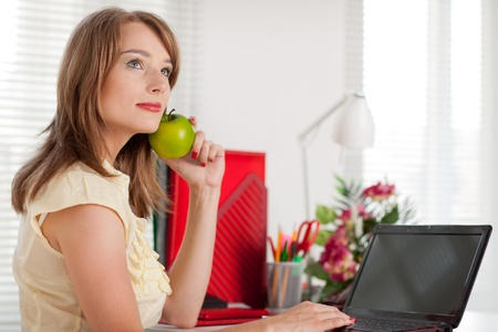 Young businesswoman with laptop sits at the table at the office. photo