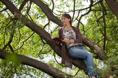 The beautiful young woman in park with the book. photo