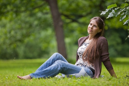 Young beautiful woman with earphones sits on the green grass  in the park. photo