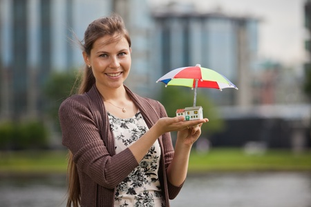 Young businesswoman stands with model of house and umbrella. Concept of buying and insuring real estate. photo