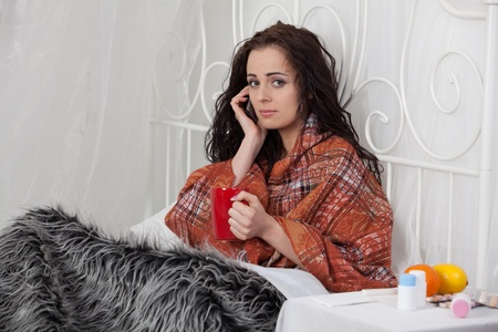 The sick unhappy young woman lies in a bed. Call of the doctor on the house. Stock Photo - 9917980