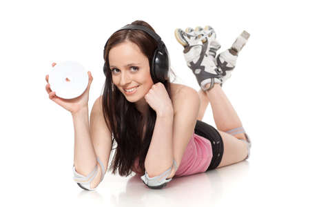 Young woman in rollerskates with earphones and a compact disc on a white background. Music for sports. photo