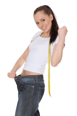 The beautiful young woman in old jeans after losing weight on a white background. Concept of healthy lifestyle. photo