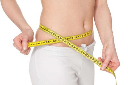 metro medir: Joven mide un volumen de cintura sobre un fondo blanco.  Concepto de estilo de vida saludable.