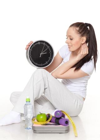 Sportieve jonge vrouw met klok, weegschaal, dumbbells en appel op een witte achtergrond. Tijd om af te slanken.