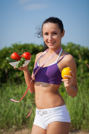 Sporty young woman with measuring tape and vegetables. Outdoors. Concept of healthy lifestyle. photo