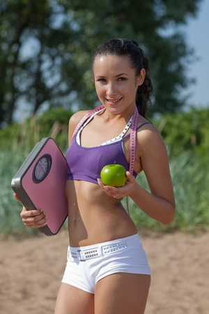 Sporty young woman with scales and green apple. Outdoors. Concept of healthy lifestyle. photo