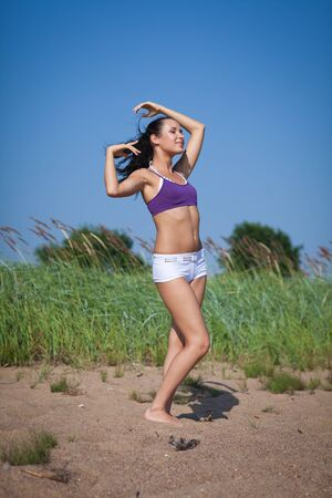 Young beautiful  woman dances on summer day. Outdoors. photo
