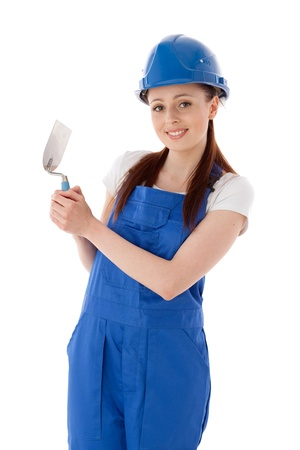 Young woman in  coverall with trowel on a white background. Female construction worker. photo