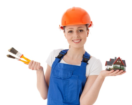 Young woman in  coverall with paintbrushes and model of house on a white background. Female construction worker. photo