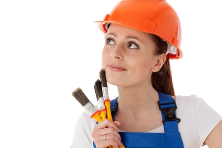 Portrait of young woman in  helmet with paintbrushes on a white background. Female construction worker. photo