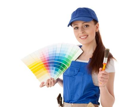 decorando: Mujer joven en sobretodo con una gu�a de colores y pinceles sobre un fondo blanco. Foto de archivo