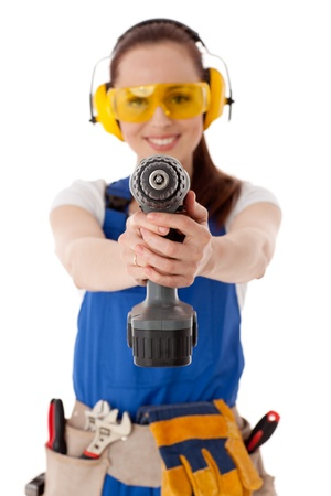 Young woman in  coverall with screwdriver on a white background. Selective focus on screwdriver photo