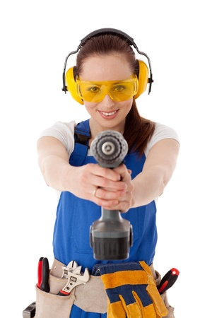 power wrench: Young woman in  coverall with screwdriver on a white background. Female construction worker.