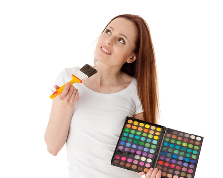 Beautiful young woman with cosmetic palette and paintbrush on a white background. photo