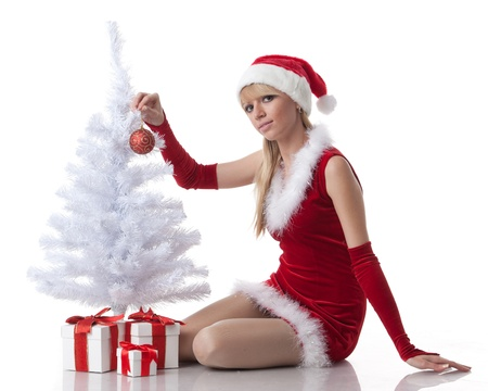 The beautiful girl with a gift in a Santas cap sits near a Christmas tree on a white background. photo