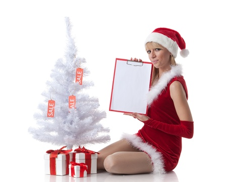 The beautiful girl with a gift in a Santa's cap sits near a Christmas tree on a white background. Stock Photo - 10623590
