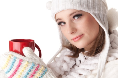 Young beautiful woman in winter warm clothes with red cup on a white background. photo