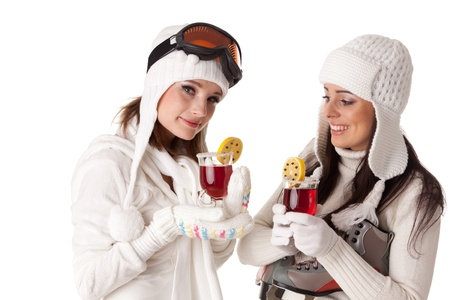 Beautiful young women in winter clothes with skates and skis drink mulled wine on a white background. Winter vacation.