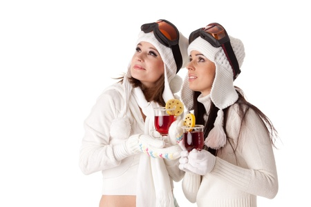 Beautiful young women in winter clothes and ski glasses drink mulled wine on a white background. Stock Photo
