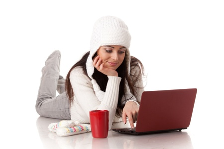 computer user: Beautiful young  woman in winter clothes with laptop lies on a white background. Stock Photo